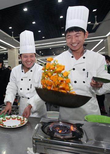 周活动中,两名大学生在烹饪美食.新华社发(刘东岳 摄)-天津上图片
